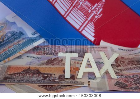 Taxation signage with Cambodian notes and flag.