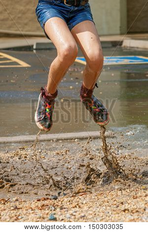 The bottom half of a girl jumping in a muddly puddle in the median of a parking lot. She is wearing jean shorts and colorful shoes and the muddy water is spraying up with her feet.