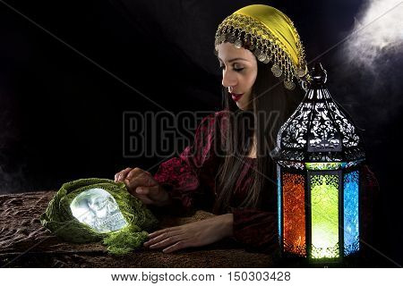 Female psychic or fortune teller holding a crystal skull trying to communicate with the dead