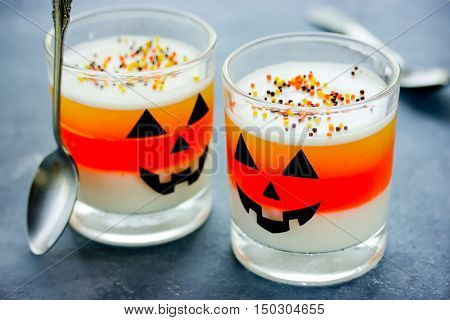 Halloween food idea - frozen dessert in jack-o'-lantern decorated glasses candy corn jello
