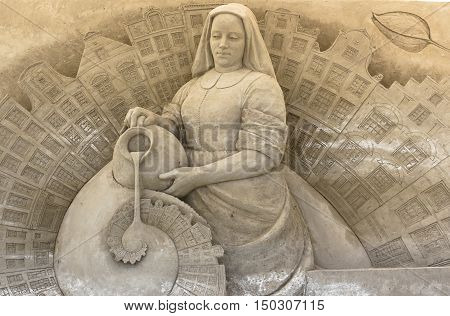 Sand sculpture of a peasant woman with a jar