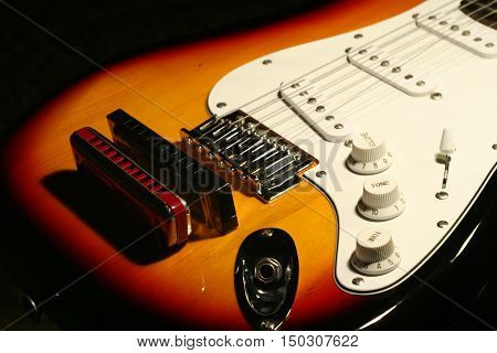 Vintage Electric Guitar With Harmonica On Black Background