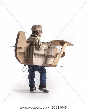Child is flying away on hand made cardboard plane. Back view.