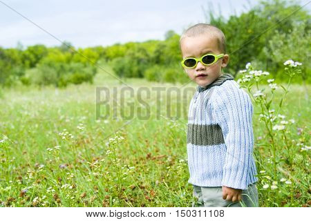Child standing in meadow wearing sunglasses outdoors
