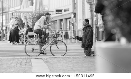 INNSBRUCK AUSTRIA - NOVEMBER 1st 2015: Refugee begging for help in the streets of Innsbruck with people walking by.