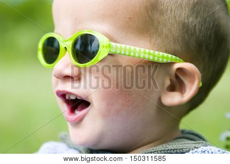 Young toddler wearing bright yellow sunglasses outdoors