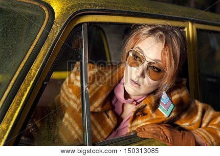 1970s vintage lady sitting in a retro car