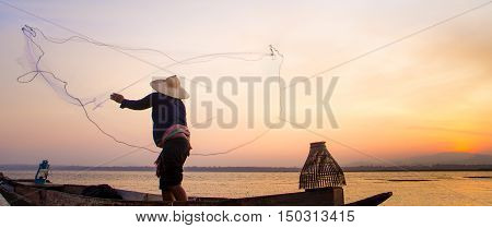 Silhouette Of Traditional Fishermen Throwing Net Fishing Lake At Sunrise Time.(the Casting People Li