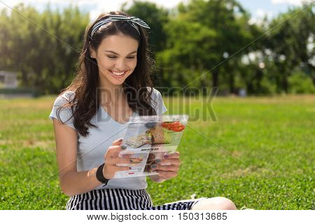 Look for receipt. Cheerful delighted charming young woman using tablet and surfing the Internet while sitting on the grass
