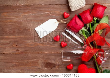 Valentines day roses bouquet, candy hearts and champagne glasses on wooden table. Top view with copy space