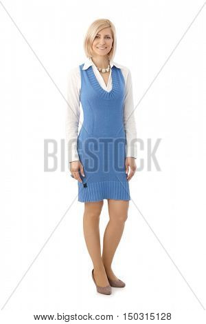 Full size portrait of happy casual blonde caucasian businesswoman standing in front of white background. Smiling, looking at camera.