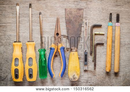 Screwdriver pliers trowel cutter hex wrench chisels on wooden table