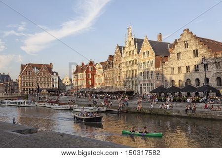 Ghent, Belgium, 27 august 2016: canoe and boats in river Leie in medieval centre in belgian town of ghent at sunset