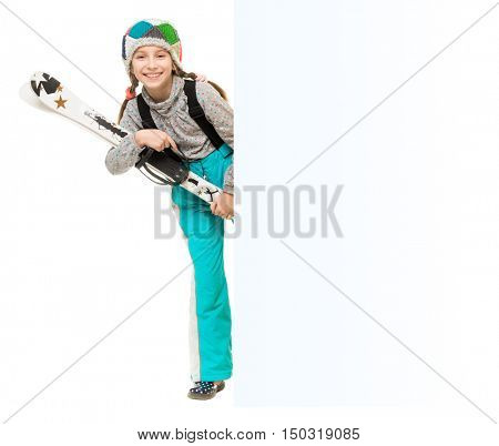 smiling little girl with skis peeking from behind an empty blank isolated on white background
