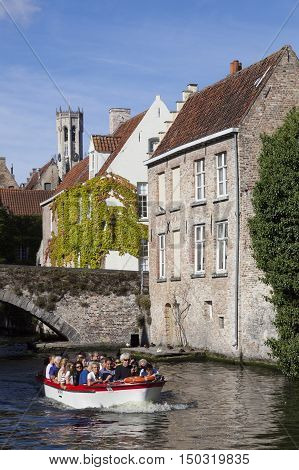 Maarssen, Netherlands, 30 september 2016: old houses and tourist boat in canal near bridge in centre of medieval Brugge in Belgium with blue sky in summer