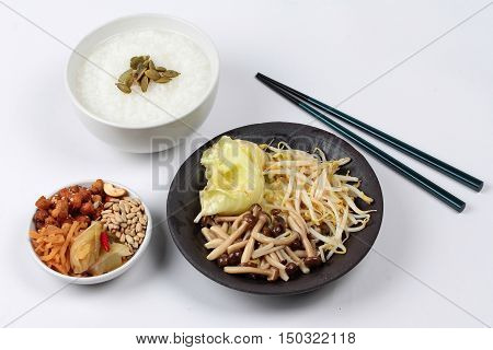 Rice gruel and fried mixed vegetable served side dish.  (topped roasted pumpkin kernel and  fried mushroom, bean sprouts,cabbage served side disk as bean cabbage,sweet radish and pickle )