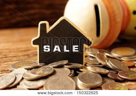 many coins with wood house and worlding sale concept idea save for purshase house.