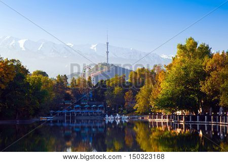 Amusement park in the morning. Reflections of trees in the lake. TV tower and snowy mountains in the background.