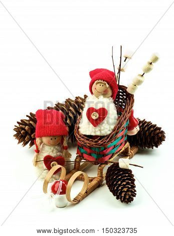 Christmas Decoration Concept with Handmade Dolls in Knit Hats Fir Cones Sleigh and Marshmallows on Wooden Sticks closeup on White background. Retro Styled