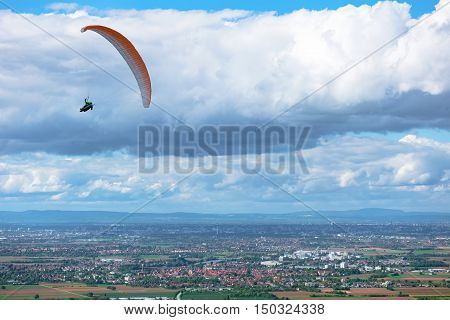 Paraglider flying over fields and towns - scenic view