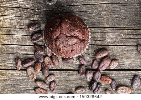 The tasty chocolate muffins and cocoa beans.on old wooden table. Top view.