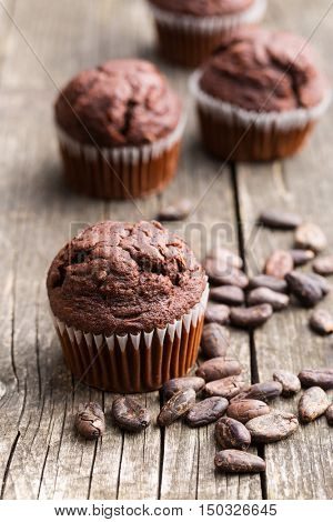 The tasty chocolate muffins and cocoa beans on old wooden table.