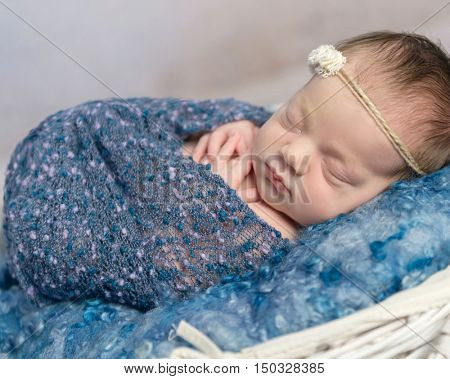 cute newborn baby girl in blue baby soft sleeping in a white wicker basket