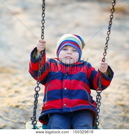 Cute little kid boy having fun with chain swing on outdoor playground. child swinging on warm sunny spring or autumn day. Active leisure with kids. Boy wearing colorful clothes
