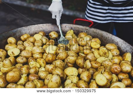 Country fair cooking. Roasted potatoes cooked by vendor outdoors in big metal cauldron pot. Cookout vegetable meals. Fresh organic, healthy snack, potatoes on grill flame. Street food, fast food.