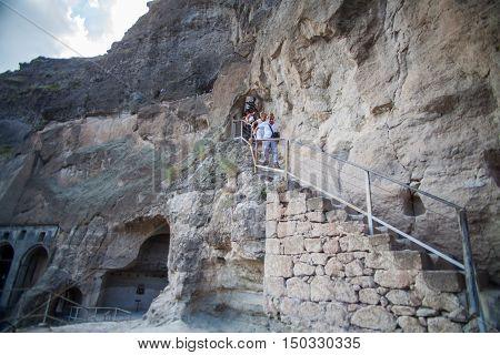 Vardzia Georgia - September 21 2016: Color image of some cave dwellings in Vardzia Georgia and some tourists.