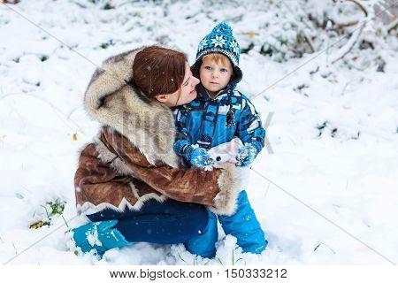 Winter portrait of kid boy and mother in colorful clothes, outdoors during snowfall. Active outoors leisure with children in winter on cold snowy days. Happy woman and son having fun with snow in forest
