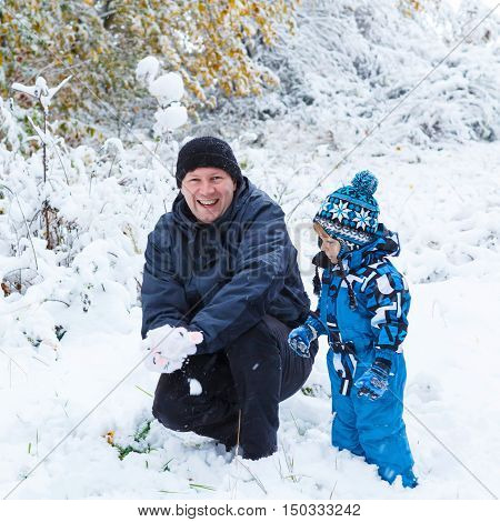 Winter portrait of kid boy and dad in colorful clothes, outdoors during snowfall. Active outoors leisure with children in winter on cold snowy days. Happy man and son having fun with snow in forest