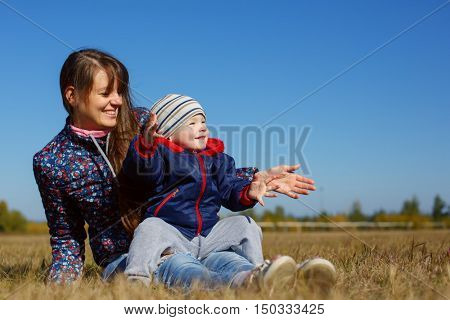 Happy young beautiful mather with smiling baby on nature outdoor