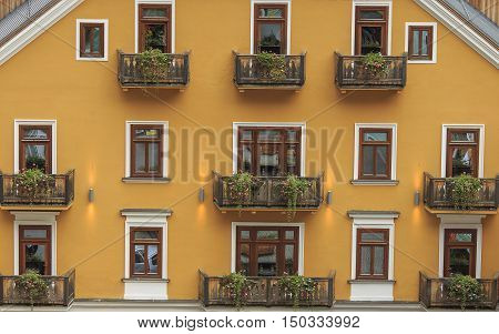 Facade of the hotel yellow color with beautiful balconies in Hallstatt Austria.