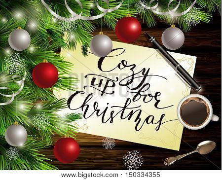 Christmas New Year design dark wooden background with christmas tree and silver and red balls and handwritten Cozy up for Christmas coffee teaspoon and pen