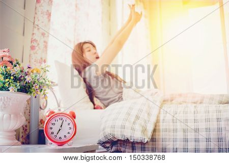 young woman wake up stretch on the bed in the morning alarm clock look so fresh day