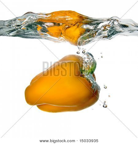 Yellow pepper dropped into water with bubbles isolated on white