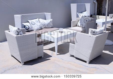 White outdoor furniture rattan armchairs on resort terrace, Greece