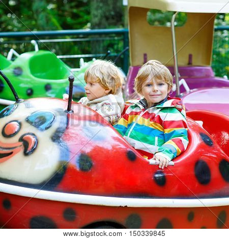 Two little funny kid boys riding on ladybug on roundabout carousel in amusement park. Happy children, twins having fun outdoors on sunny day.