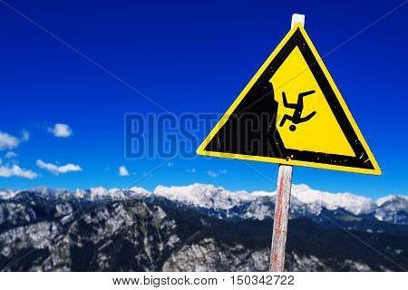 Warning sign - possible fall from the mountain cliff Julian Alps in the background