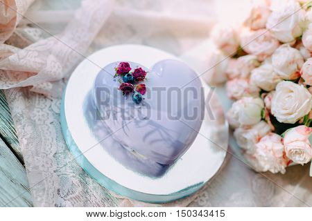 bouquet of pink roses and a cake with blue icing in the form of a heart with flowers