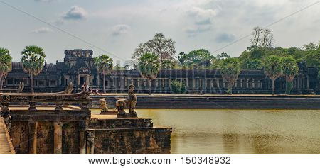 Lions guarding the main entrance to the ruins of Angkor Wat temple in the ancient city of Angkor Siem Reap Cambodia. The largest religious monument in the world.