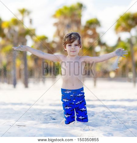 Beautiful blond little kid boy having fun on Miami beach, Key Biscayne. Happy cute child playing with sand and running near ocean.