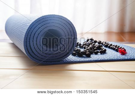 Accessories for yoga and meditation.Mat and mala beads on wooden background.