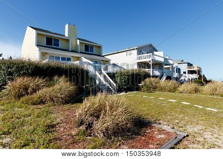 Luxury beach vacation rental homes on the green grass covered sand dunes: Sunset Beach, North Carolina