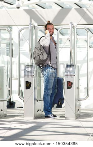 Man Standing At Station Entrance With Phone And Luggage