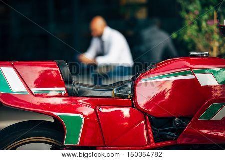 Close-up of bike seat against unfocused sitting man