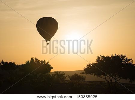 Hot-air balloon flying at sunrise. Trees silhouettes in foreground. Gold sky in background.