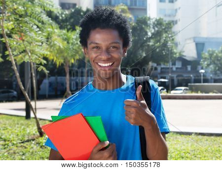 Young african american male student showing thumb outdoor in the city in the summer