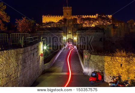Knight castle at night with the trace of motorcycle headlights